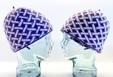 two glass mannequin heads with hats with cross hatch pattern in purple and white