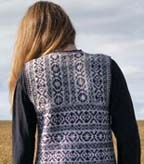 back view of model wearing the fair isle surprise vest knit in mulberry, purples, and gray