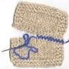 two pieces of natural wool being joined using contrasting blue yarn