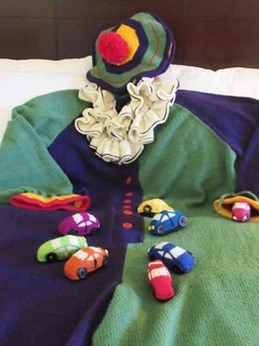knitted clown suit in blues, greens, with knitted tiny clown cars